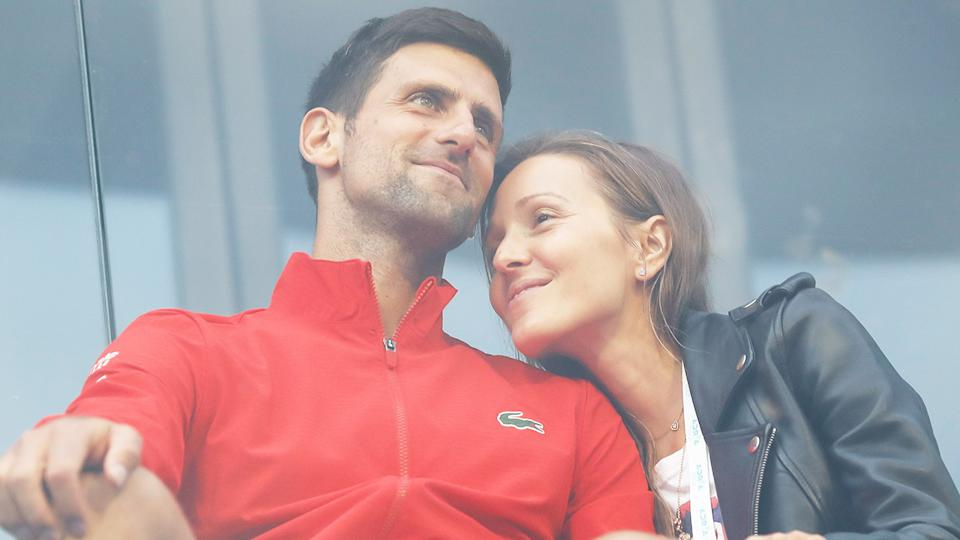 Novak Djokovic (pictured left) hugging his wife Jelena Djokovic (pictured right) in the stands.