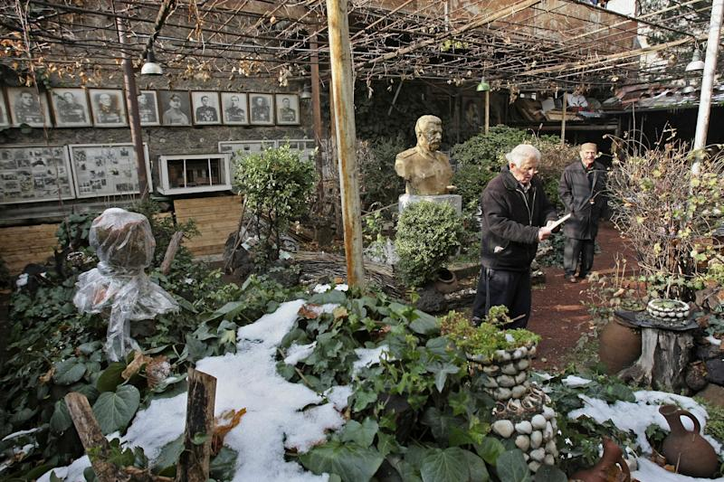 Ushangi Davitashvili, left, and his neighbor Guram Dochviri stand near the bust of Soviet dictator Josef Stalin located in the courtyard of his apartment building in the Georgian capital, Tbilisi, Friday, Dec. 21, 2012. Stalin was born in Georgia in 1879 and led the Soviet Union through decades of totalitarian reforms and political purges. (AP Photo/Shakh Aivazov)