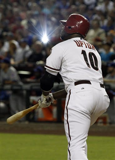Arizona Diamondbacks' Justin Upton watches his RBI double bounce over the fence against the Chicago Cubs during the seventh inning in an MLB baseball game Friday, June 22, 2012, in Phoenix.(AP Photo/Ross D. Franklin)