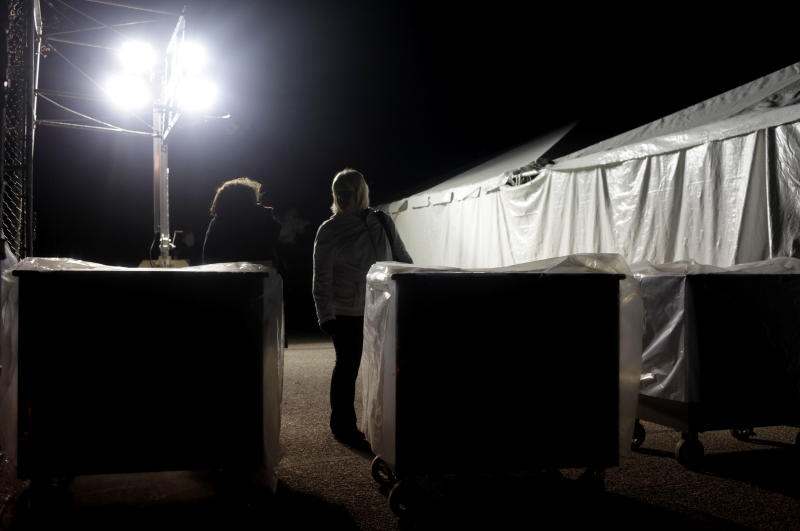 Under the lights of a generator, poll workers and voting machines voters wait outside of a tent serving as a polling site in the Midland Beach section of Staten Island, New York, on Election Day, Tuesday, Nov. 6, 2012. The original polling site, a school, was damaged by Superstorm Sandy. (AP Photo/Seth Wenig)