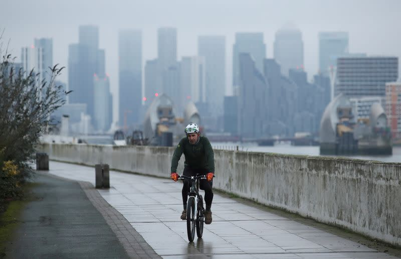 FILE PHOTO: Buildings are seen in the Canary Wharf business district, as a man cycles along a path, amid the outbreak of the coronavirus disease (COVID-19), in London