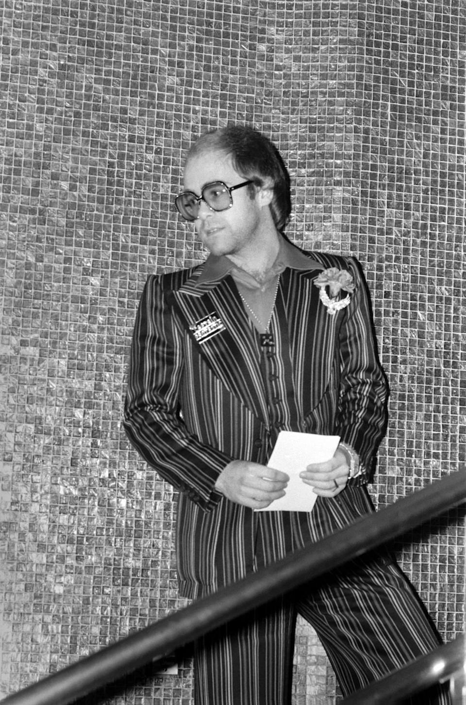 <p>Elton John photographed in 1975 wearing a striped suit with tinted sunglasses, which was very '70s relaxed chic for the musician. (Photo: Getty Images) </p>