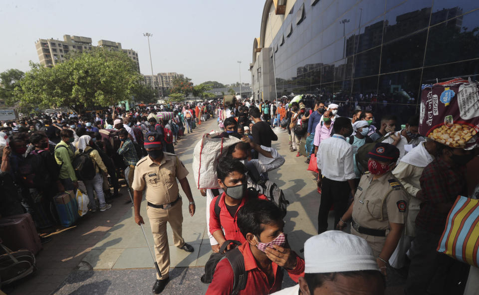People wearing masks as a precaution against the coronavirus stand in queues to board trains at Lokmanya Tilak Terminus in Mumbai, India, Wednesday, April 14, 2021. Migrant workers are swarming rail stations in India's financial capital Mumbai to go to their home villages as virus-control measures dry up work in the hard-hit region. The government of Maharashtra state imposed lockdown-like curbs on Wednesday for 15 days to check the spread of the virus. It closed most industries, businesses and public places and limited the movement of people, but didn't stop the bus, train and air services. An exodus ensued, with panicked day laborers hauling backpacks onto overcrowded trains leaving Mumbai, travel that raises fears of infections spreading in rural areas. (AP Photo/Rafiq Maqbool)