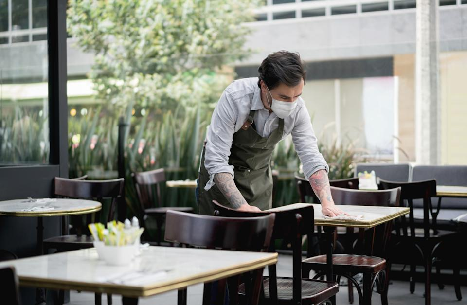 Waiter at a restaurant wearing a facemask and cleaning the tables during the COVID-19 pandemic - reopening of businesses concepts