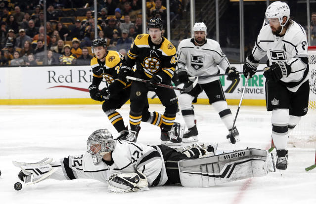 Los Angeles Kings goaltender Jonathan Quick dives after a loose puck as Boston Bruins' Danton Heinen (43) looks on during the second period of an NHL hockey game Saturday, Feb. 9, 2019, in Boston. (AP Photo/Winslow Townson)