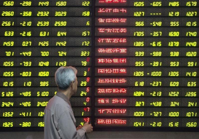 An investor looks at an electronic screen showing stock information at a brokerage house in Nanjing