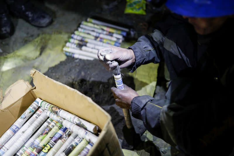 An artisanal gold miner makes dynamite sticks with newspaper before setting off an explosion inside a gold mine in La Rinconada, in the Andes