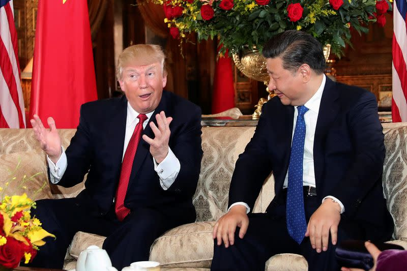 FILE PHOTO: U.S. President Donald Trump interacts with Chinese President Xi Jinping at Mar-a-Lago state in Palm Beach, Florida