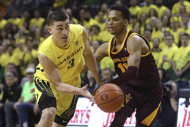 Oregon's Payton Pritchard, left, passes the ball under pressure from Arizona State's Alonzo Verge during the first half of an NCAA college basketball game in Eugene, Ore., Saturday, Jan. 11, 2020. (AP Photo/Chris Pietsch)