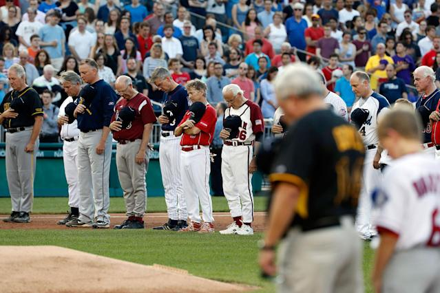 <p>Members of both congressional teams bow their heads for a moment of silence for Rep. Steve Scalise, R-La., before the Congressional baseball game, Thursday, June 15, 2017, in Washington. (Photo: Alex Brandon/AP) </p>