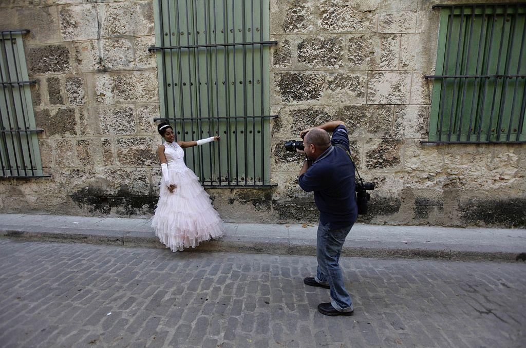 <p>Carmen Gonzalez (L) poses during a photo session in the old quarters of Havana for her quinceanera.</p>