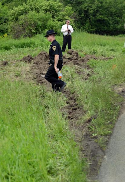 Law enforcement officials work the scene of a fatal car crash along Route 13 in Truxton, NY, Thursday, May 30, 2013. According to the Cortland County coroner, four children and three adults were killed when their minivan was hit by a trailer. Deputies say a tractor trailer carrying crushed cars was going down the highway when the hitch failed and the trailer became disconnected. The trailer slammed into a minivan with eight people inside. Four children under the age of 10 and three adults in their early 20s were killed, and a man was injured in the crash. (AP Photo/Heather Ainsworth)