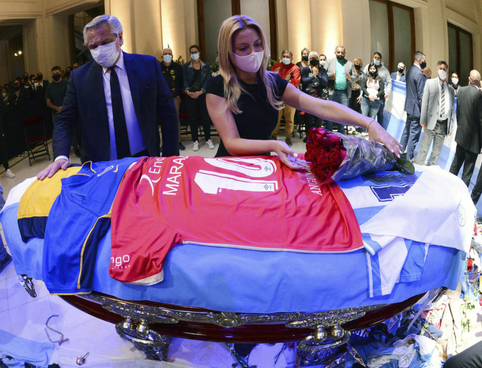 In this handout photo released by Argentina's Presidency, President Alberto Fernandez touches the coffin that contain the remains of Diego Maradona, while first lady Fabiola Yañez places a bouquet of roses on the casket adorned with his team jerseys, as they pay their final respects to Maradona, inside the presidential palace in Buenos Aires, Argentina, Thursday, Nov. 26, 2020. The Argentine soccer great who led his country to the 1986 World Cup title died of a heart attack at his home Wednesday at the age of 60. (Argentina's Presidency via AP)