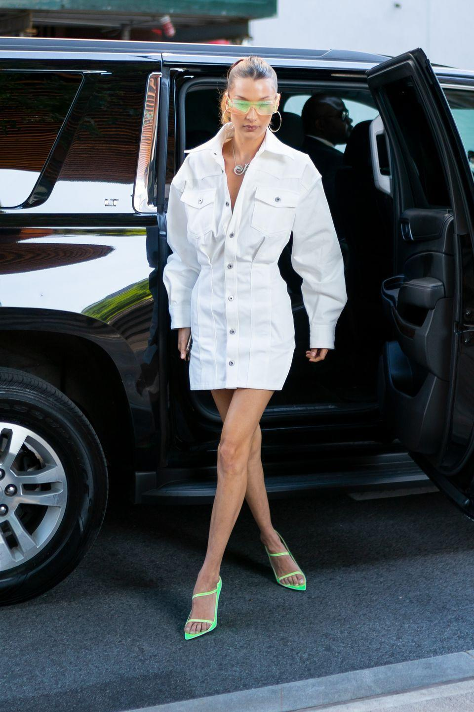 """<p>In an oversized white dress, neon green sunglasses, matching heeled sandals from <a href=""""https://www.harpersbazaar.com/fashion/designers/a27529317/rihanna-first-fenty-collection/"""" rel=""""nofollow noopener"""" target=""""_blank"""" data-ylk=""""slk:Rihanna's Fenty clothing line"""" class=""""link rapid-noclick-resp"""">Rihanna's Fenty clothing line</a>, and a custom necklace from <a href=""""https://nigoratabayer.com/"""" rel=""""nofollow noopener"""" target=""""_blank"""" data-ylk=""""slk:Nigora Tabayer"""" class=""""link rapid-noclick-resp"""">Nigora Tabayer</a> while exiting her car in Brooklyn, New York.</p>"""