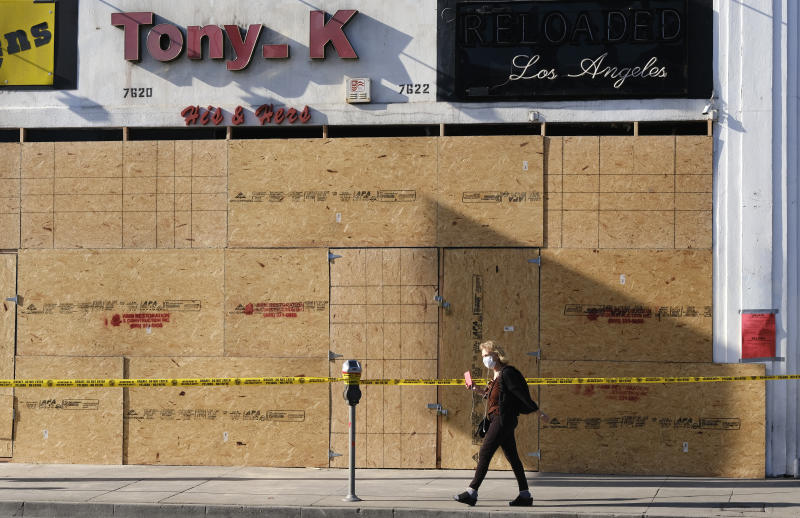 A woman takes photos of a boarded-up store after mass demonstrations looted the area on Saturday night over the death of George Floyd in the Fairfax district of Los Angeles, Monday, June 1, 2020. (AP Photo/Richard Vogel)