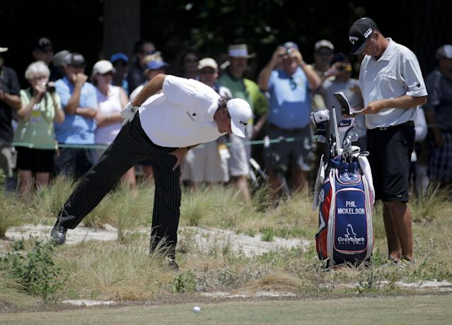 Phil Mickelson, left, looks at his ball in waste area on the 18th hole during a practice round for the U.S. Open golf tournament in Pinehurst, N.C., Tuesday, June 10, 2014. The tournament starts Thursday. (AP Photo/Eric Gay)