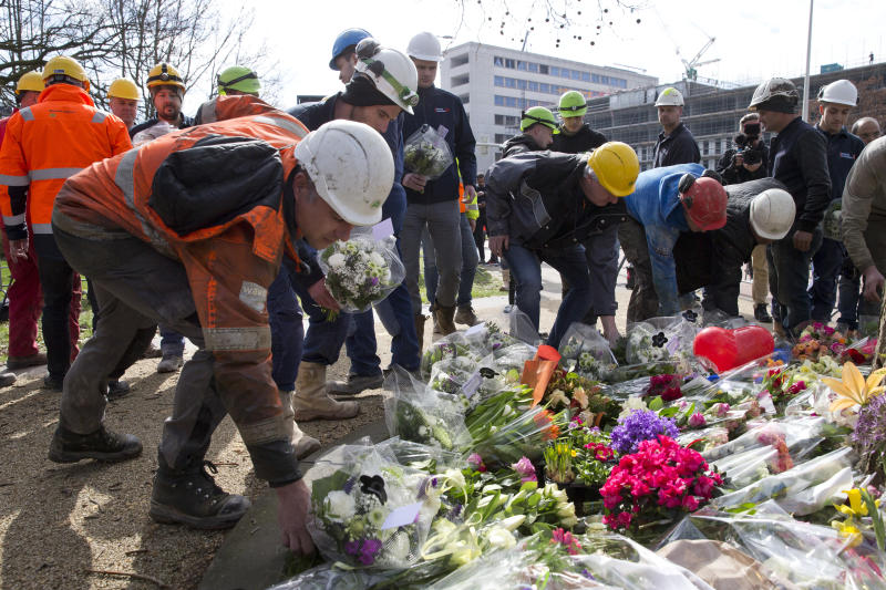 Construction workers who witnessed Monday's shooting incident in a tram put flowers at the site in Utrecht, Netherlands, on Tuesday. (ASSOCIATED PRESS)