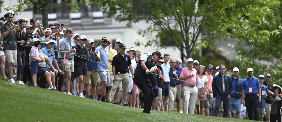 Phil Mickelson hits a shot from a hill near the 15th green during the second round of the Wells Fargo Championship golf tournament at Quail Hollow Club in Charlotte, N.C., Friday, May 7, 2021. (Jeff Siner/The Charlotte Observer via AP)