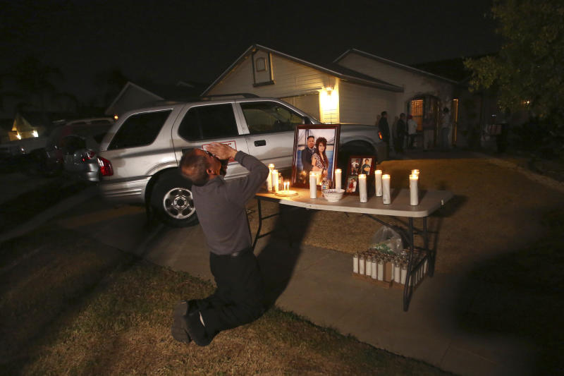 """In this photo taken Monday, Nov. 18, 2019, Neej Xiong, uncle of shooting victim Kour Xiong, prays in front of a memorial during a candlelight vigil in Fresno, Calif. A close-knit Hmong community was in shock after gunmen burst into a California backyard gathering and shot 10 men, killing four. """"We are right now just trying to figure out what to do, what are the next steps. How do we heal, how do we know what's going on,"""" said Bobby Bliatout, a community leader. (Larry Valenzuela/The Fresno Bee via AP)"""