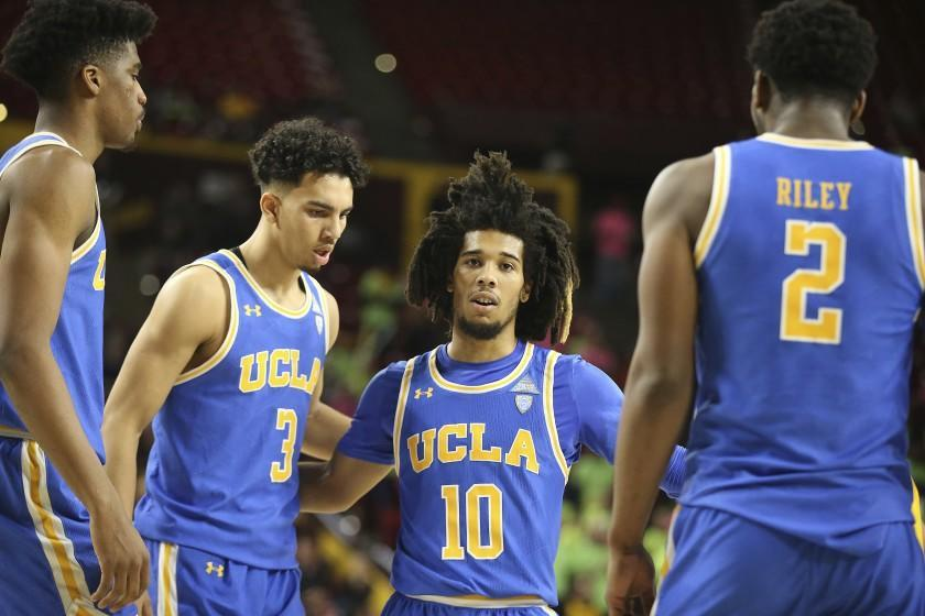 With his team down by double digits to Arizona State, UCLA's Tyger Campbell (10) gathers his teammates Chris Smith, left, Jules Bernard (3) and Cody Riley (2) during the second half of an NCAA college basketball game, Thursday, Feb. 6, 2020, in Tempe, Ariz. (AP Photo/Darryl Webb)
