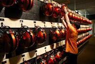 Oregon Staters football equipment coordinator Arnie Alcanta hangs wide receiver Brandin Cooks' helmet on a hook as Beavers unveiled new orange uniforms before an NCAA college football game against Southern California at Reser Stadium in Corvallis, Ore., Friday, Nov. 1, 2013. (AP Photo/The Oregonian, Randy L. Rasmussen)