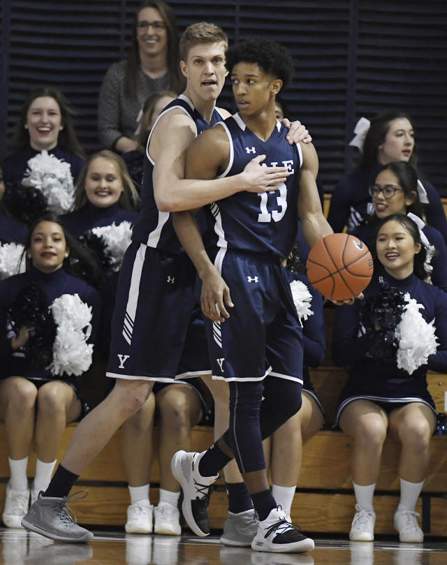 Yale's Blake Reynolds, left, embraces teammate Trey Phills during the first half of an NCAA college basketball game for the Ivy League championship against Harvard at Yale University in New Haven, Conn., Sunday, March 17, 2019, in New Haven, Conn. (AP Photo/Jessica Hill)