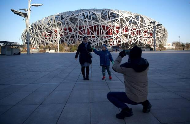 People take pictures in front of the Birds Nest stadium, the venue for opening and closing ceremonies for the 2022 Winter Olympics, in Beijing. (AFP via Getty Images - image credit)