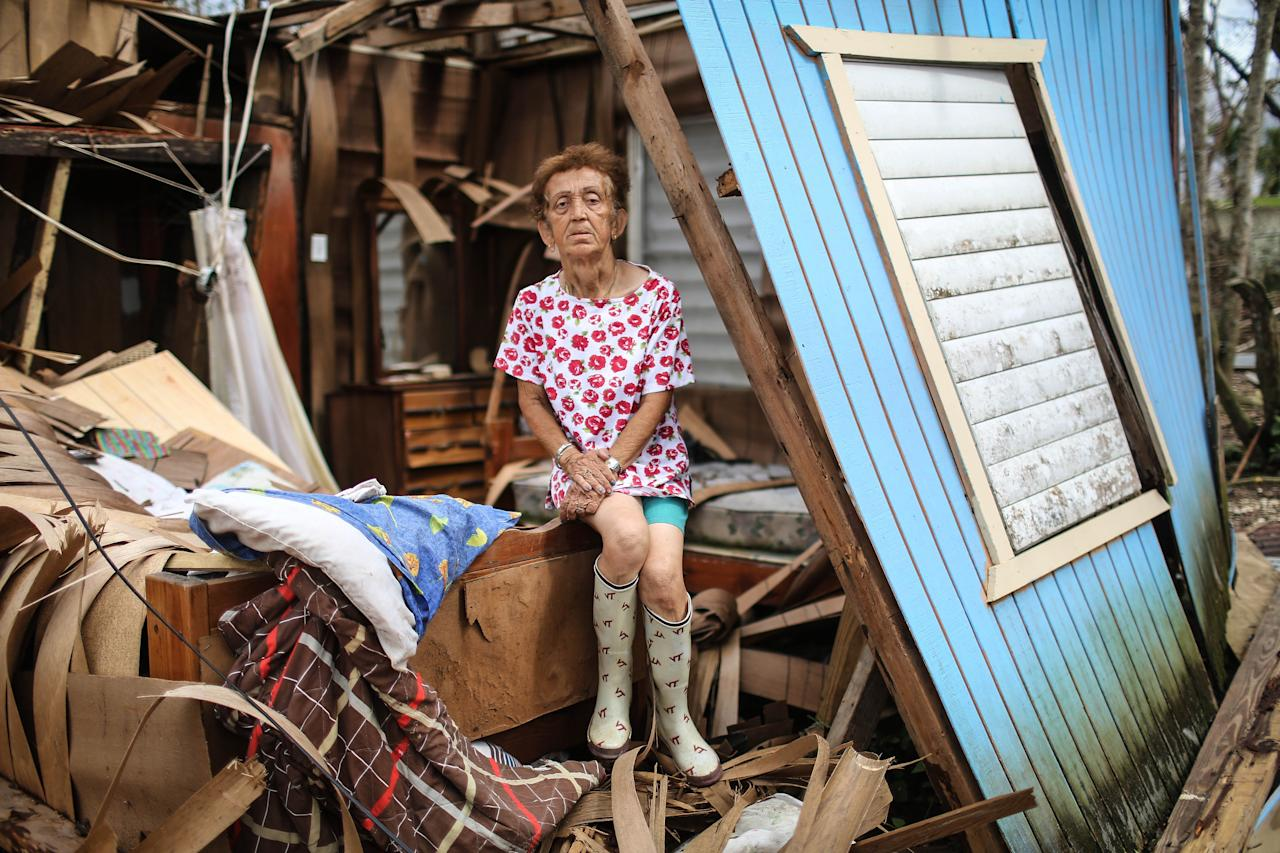 <p>Sonia Torres poses in her destroyed home, while taking a break from cleaning, three weeks after Hurricane Maria hit the island, on Oct. 11, 2017 in Aibonito, Puerto Rico. The area is without running water or grid power as a nightly curfew remains in effect. Despite multiple visits from FEMA, the town has yet to receive any FEMA aid. Only 10.6 percent of Puerto Rico's grid electricity has been restored. Puerto Rico experienced widespread damage including most of the electrical, gas and water grid as well as agriculture after Hurricane Maria, a category 4 hurricane, swept through. (Photo: Mario Tama/Getty Images) </p>