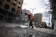 Palestinian municipal workers clean the streets following a cease-fire reached after an 11-day war between Gaza's Hamas rulers and Israel, in Gaza City, Friday, May 21, 2021. (AP Photo/Khalil Hamra)