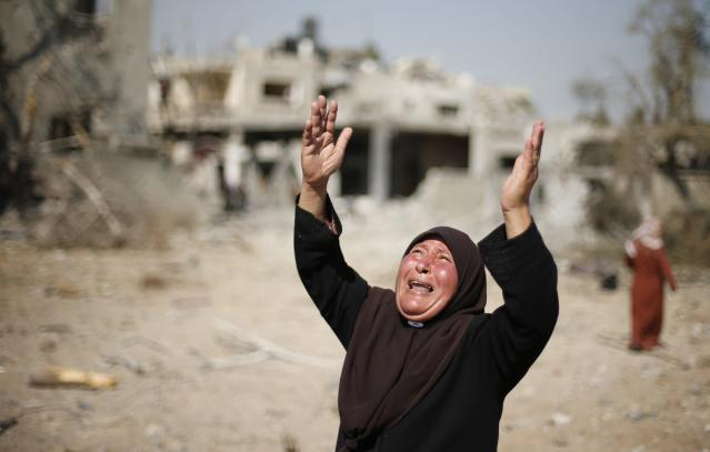 A Palestinian woman reacts upon seeing her destroyed house in Beit Hanoun town, which witnesses said was heavily hit by Israeli shelling and air strikes during Israeli offensive, in the northern Gaza Strip August 1, 2014. A three-day ceasefire between Israel and Palestinian militant groups in the Gaza Strip went into effect on Friday, with negotiators due to travel to Cairo to discuss a longer-term solution. But some two hours after the truce began, a Reuters photographer and the Gaza Interior Ministry said Israeli tanks opened fire in the southern Rafah area, and Hamas media reported four people were killed. The Israeli military had no immediate comment. REUTERS/Suhaib Salem (GAZA - Tags: POLITICS CIVIL UNREST TPX IMAGES OF THE DAY)
