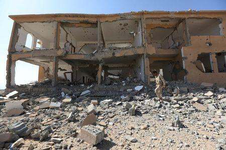 A soldier loyal to Yemen's President Abd-Rabbu Mansour Hadi walks past a destroyed building at the Mass army barracks after the pro-Hadi forces took it from Houthi rebels in the country's northwestern province of Marib December 18, 2015. REUTERS/Ali Owidha