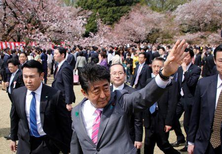 Japan's PM Abe waves to guests during a cherry blossom viewing party at Shinjuku Gyoen park in Tokyo
