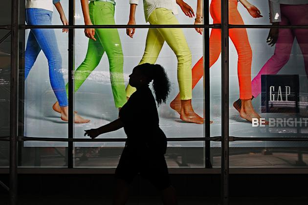 A woman walking pass the display window of a Gap Store in Time Square, New York City. (photo: Siemond Chan)