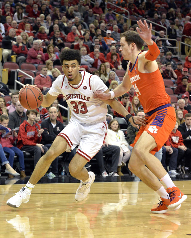 FILE - In this Feb. 16, 2019, file photo, Louisville forward Jordan Nwora (33) attempts to drive past the defense of Clemson forward Elijah Thomas (14) during the second half of an NCAA college basketball game in Louisville, Ky. The return of forwards Jordan Nwora and Steven Enoch could make the Cardinals a top-10 team heading into next season. (AP Photo/Timothy D. Easley, File)