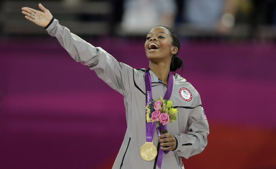 U.S. gymnast Gabrielle Douglas acknowledges the crowd after receiving her gold medal during the artistic gymnastics women's individual all-around competition at the 2012 Summer Olympics, Thursday, Aug. 2, 2012, in London. (AP Photo/Gregory Bull)