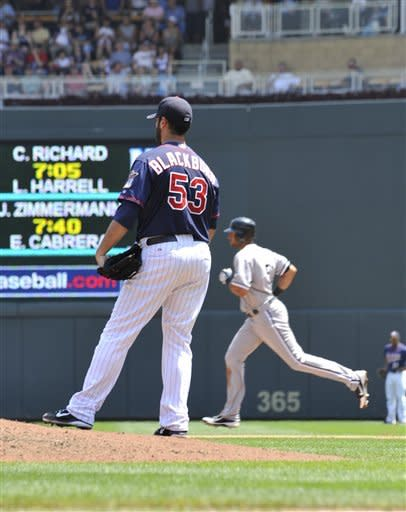 Minnesota Twins pitcher Nick Blackburn, left, gives up a solo home run to Chicago White Sox' Alex Rios, right, in the fifth inning of a baseball game Wednesday, June 27, 2012 in Minneapolis. Rios' home run followed a three-run blast by Adam Dunn. (AP Photo/Jim Mone)