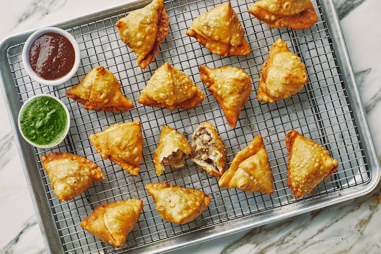 """These deliciously savory crispy fried samosas from <a href=""""https://www.ammanyc.com/"""" rel=""""nofollow"""" target=""""_blank"""">Amma</a> restaurant in New York feature a spiced potato filling packed with bright, lemony flavor thanks to coriander (whole seeds <em>and</em> ground) and amchur. Serve them with homemade or store-bought tamarind or cilantro chutney or raita alongside for dipping. If you're having trouble forming the samosas, we like this video for <a href=""""https://www.youtube.com/watch?v=0z3kSj184oo"""" rel=""""nofollow"""" target=""""_blank"""">the step-by-step process</a>. <a href=""""https://www.bonappetit.com/recipe/ammas-samosas?mbid=synd_yahoo_rss"""">See recipe.</a>"""