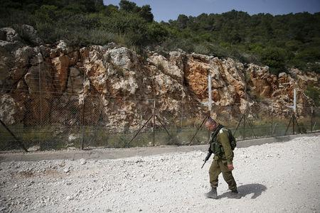 FILE PHOTO: An Israeli soldier walks near the area where the Israeli army is excavating part of a cliff to create an additional barrier along its border with Lebanon, near the community of Shlomi in northern Israel April 6, 2016. REUTERS/Ronen Zvulun/File Photo