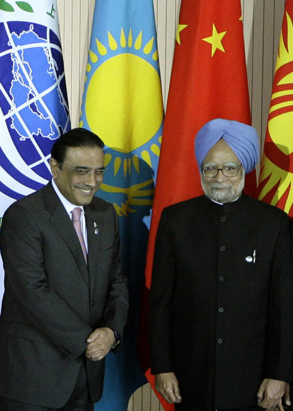 FILE - In this June 16, 2009 file photo, Pakistan's President Asif Ali Zardari, left, and Indian Prime Minister Manmohan Singh pose for a photo during a summit of the Shanghai Cooperation Organization in the Ural Mountains city of Yekaterinburg, Russia. Zardari's trip to India on Sunday, April 8, 2012, is a milestone in the warming relations between the neighbors. But, officially, he is just sharing a quick lunch with the India's leader on his way to visit a Muslim shrine. (AP Photo/Mikhail Metzel, File)