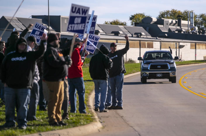 John Deere Drivetrain Operations workers in Waterloo, Iowa, cheer on the picket line as passing cars honk in support as the UAW officially started its strike on Thursday, Oct. 14, 2021. (Chris Zoeller/The Courier via AP)
