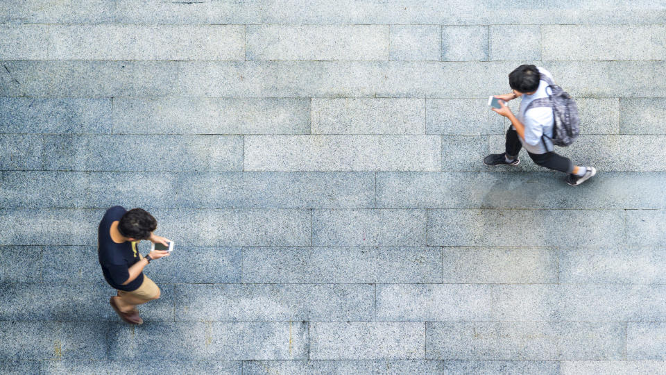 Aerial top view of people walking on a street while using their smartphones. (Photo: Getty Images)