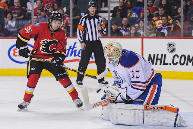 CALGARY, AB - JANUARY 31: Johnny Gaudreau #13 of the Calgary Flames takes a shot on Ben Scrivens #30 of the Edmonton Oilers during an NHL game at Scotiabank Saddledome on January 31, 2015 in Calgary, Alberta, Canada. (Photo by Derek Leung/Getty Images)