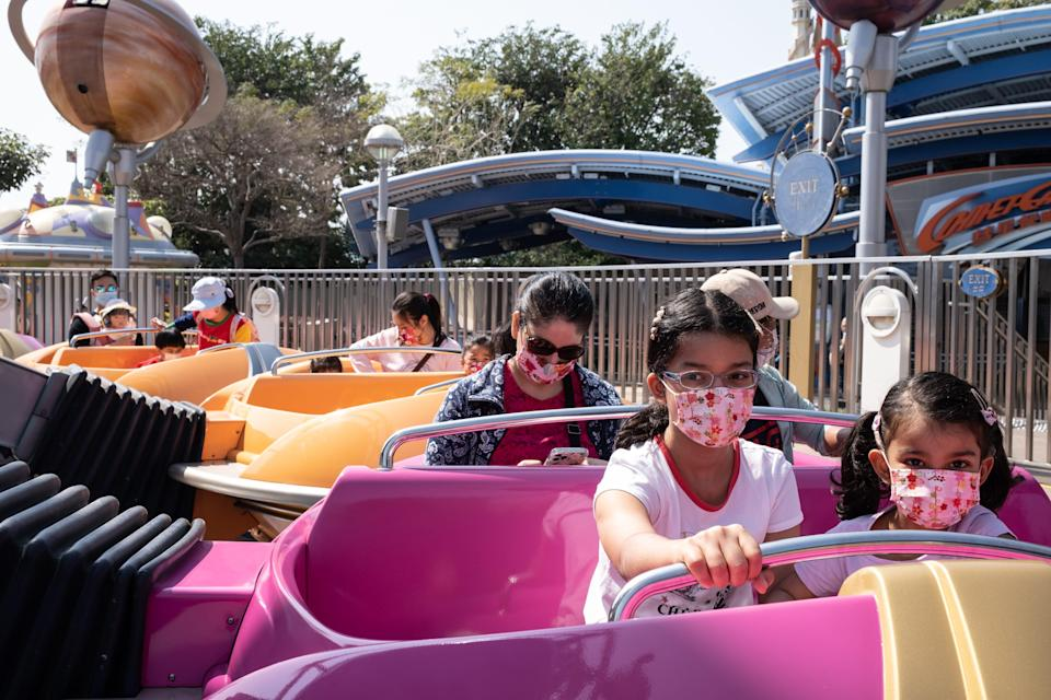 This image shows kids on a ride with face masks on.