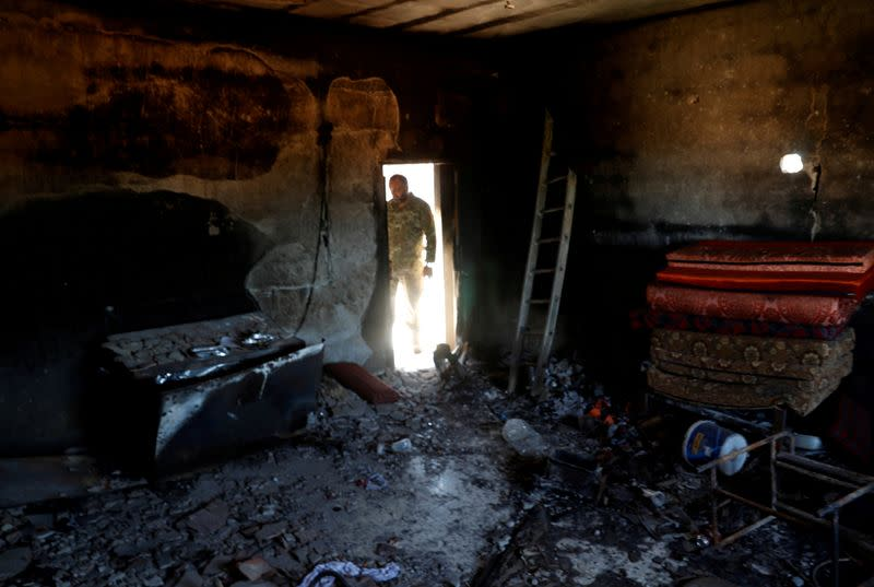 FILE PHOTO: A fighter loyal to Libya's U.N.-backed government (GNA) looks at a room burned during clashes with troops loyal to Khalifa Haftar in Wadi Rabiya neighbourhood at outskirts of Tripoli