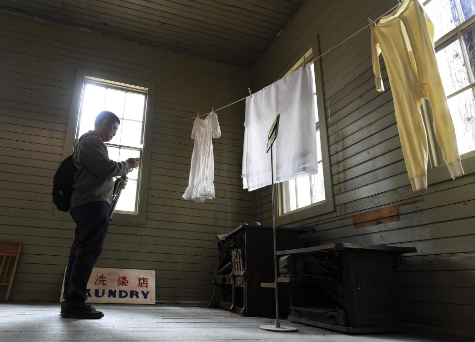 In this Friday, Oct. 1, 2021, photo Ricky Leo of Thousand Oaks takes a photo of old stoves in the restored 1917 Chinese laundry building at Wawona at Wawona in Yosemite National Park, Calif. Officials unveiled on Friday a new sign and exhibit inside a building originally used as a laundry by Chinese workers at Yosemite's Wawona Hotel, formally recognizing Chinese Americans' contributions to the national park's history. (John Walker/The Fresno Bee via AP)