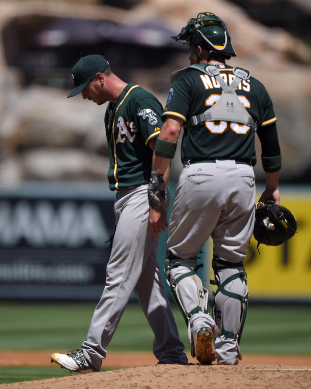 Oakland Athletics starting pitcher Scott Kazmir, left, walks off the mound after walking in a run as catcher Derek Norris looks on during the second inning of a baseball game against the Los Angeles Angels, Sunday, Aug. 31, 2014, in Anaheim, Calif. Kazmir walked in two runs during the inning. (AP Photo/Mark J. Terrill)
