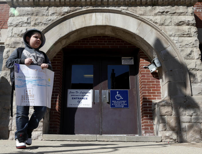 A lone student walks outside Lafayette Elementary School in Chicago with a poster asking that the school not be closed on Thursday, March 21, 2013, in Chicago. At Lafayette, a school in the Humboldt Park neighborhood where 95 percent of its 483 students come from low-income families, the principal read teachers a letter from the district Thursday saying the school is among those it plans to close under a contentious plan that opponents say will disproportionately affect minority students in the nation's third largest school district. (AP Photo/Charles Rex Arbogast)