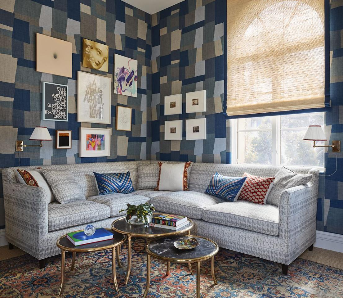 "<p>The Los Angeles-based interior and textile designer dubbed this funky, first-floor lounge Blue Paradise. ""It's located right off the soaring living room, so I envisioned this space as a more intimate, 'moodier' room for entertaining,"" says Peter Dunham of <a rel=""nofollow"" href=""http://www.peterdunham.com/"">Peter Dunham Design</a>. ""I want people to ask themselves: 'what's going on in here?'"" The walls are wrapped in Dunham's cubist Collage fabric, and serve as a graphic backdrop for mix of modern art. The sectional is upholstered in the designer's Souk fabric, and the ""beaten up old Persian carpet gives the room an Old World, inherited feel,"" he notes.</p><p><em><u>Drapery fabrication and window shades by <a rel=""nofollow"" href=""https://www.theshadestore.com/"">The Shade Store</a>.</u></em></p>"