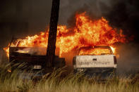 Flames consume vehicles in a wrecking yard as the Dixie Fire burns in Chester, Calif., on Wednesday, Aug. 4, 2021. The region is under red flag fire warnings due to dry, windy conditions. (AP Photo/Noah Berger)