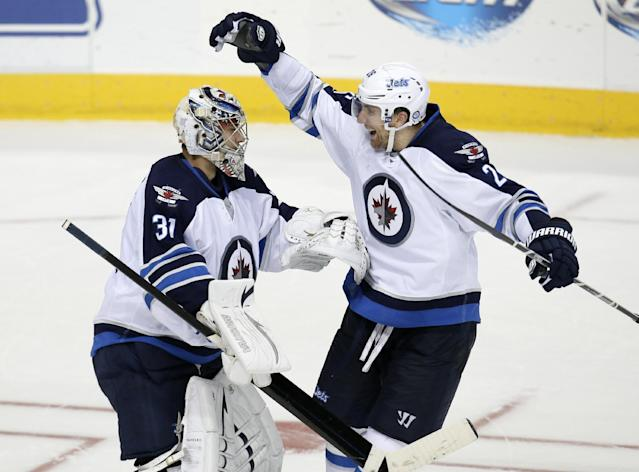 Winnipeg Jets' Ondrej Pavelec (31), of Czech Republic, celebrates with Blake Wheeler (26) after a shootout with the Dallas Stars in overtime of an NHL hockey game, Saturday, Oct. 26, 2013, in Dallas. Pavelec denied the Stars on all three attempts in the 2-1 Jets win. (AP Photo/Tony Gutierrez)
